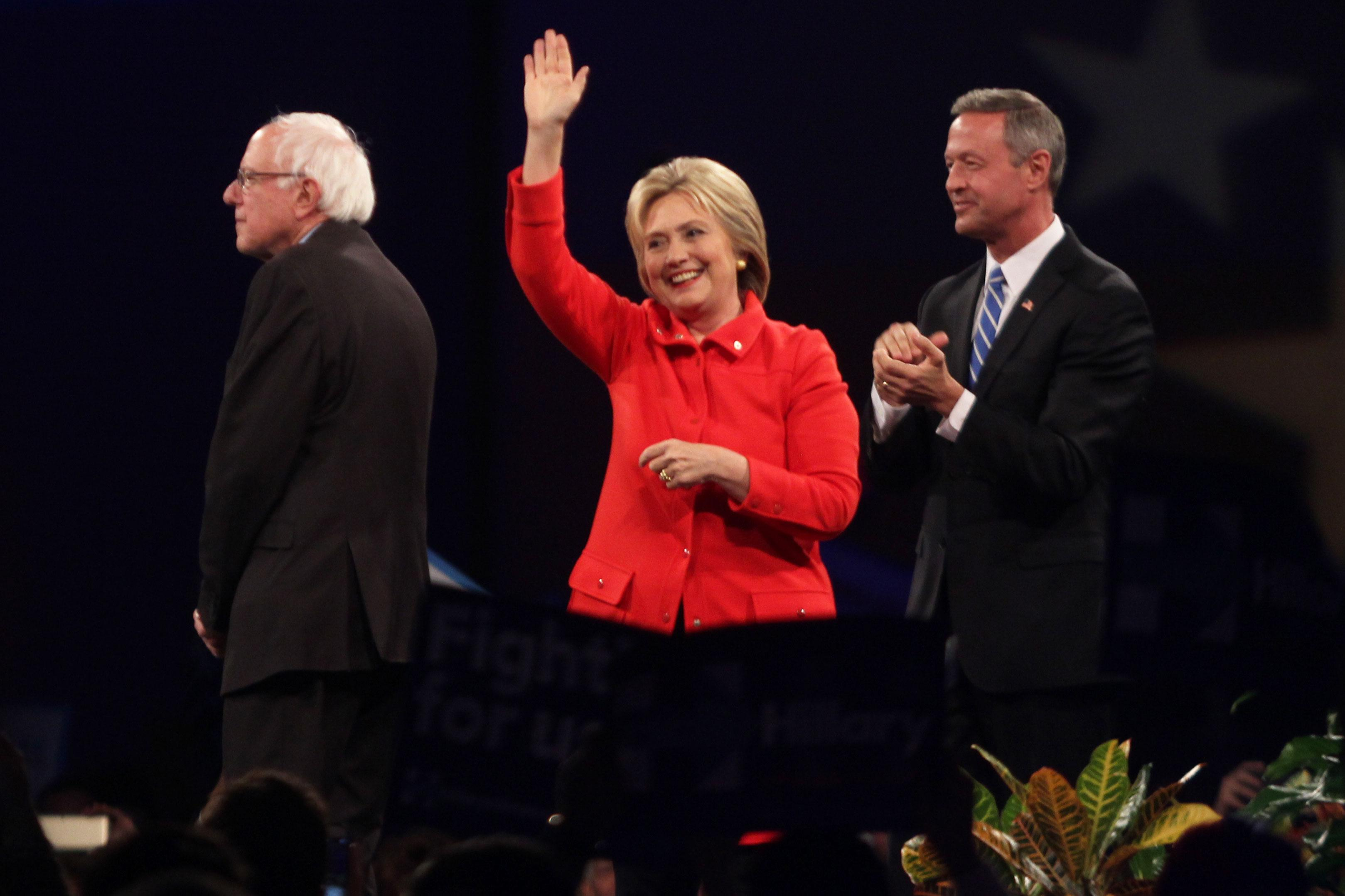 The three Democrat candidates, Bernie Sanders (left), Hillary Clinton (center) and Martin O'Malley (right), take the stage before the start of the keynote speeches.