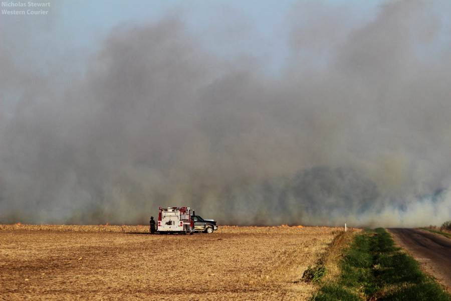 Dense smoke grows from a large field fire. Firefighters prepare to tackle the fire.