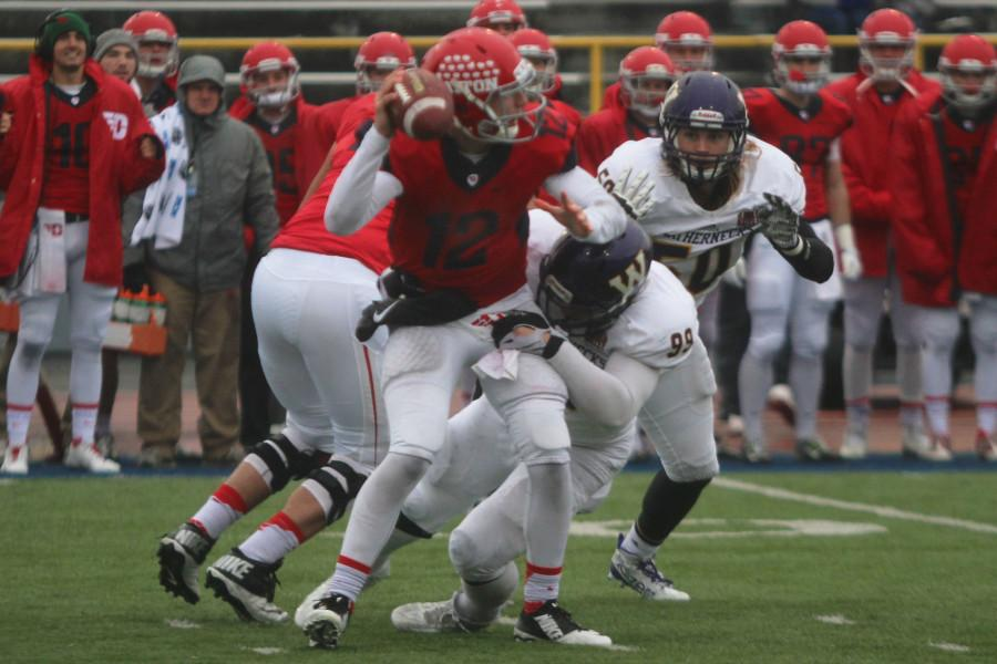 Dayton quarterback Alex Jeske is sacked by a strong Leatherneck defensive attack.