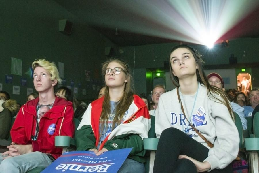 Jonah Guy (left), Deni Baird (center) and Lenin Cardwell (right), supporters of Sen. Bernie Sanders, watch the debate during a watch party at the Varsity Theater in Des Moines, Iowa.