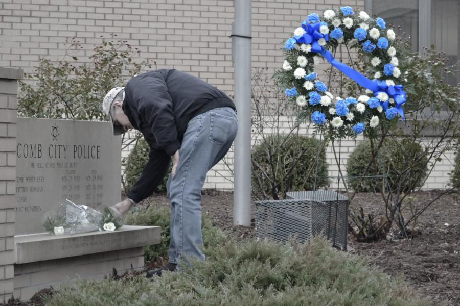 Retired Macomb Police Lt. Larry Carlson lays a flower in remembrance of his friend and co-worker Officer McFadden.