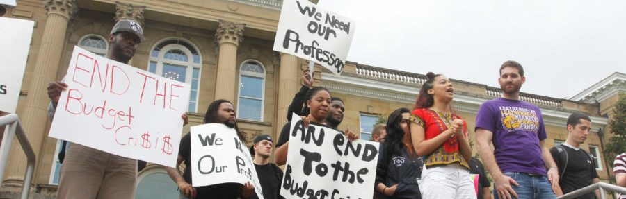 Students+and+faculty+participating+in+the+walkout+stand+outside+of+Sherman+Hall+in+protest+of+the+10-month+state+budget+impasse%2C+which+has+resulted+in+layoffs+and+funding+reductions+on+Tuesday.