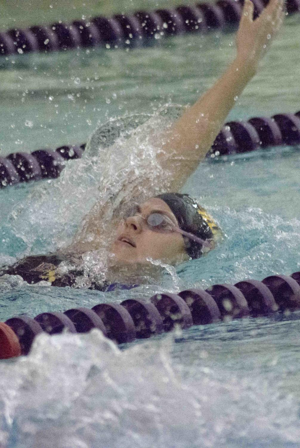 Leatherneck swimmer competes in backstroke event.
