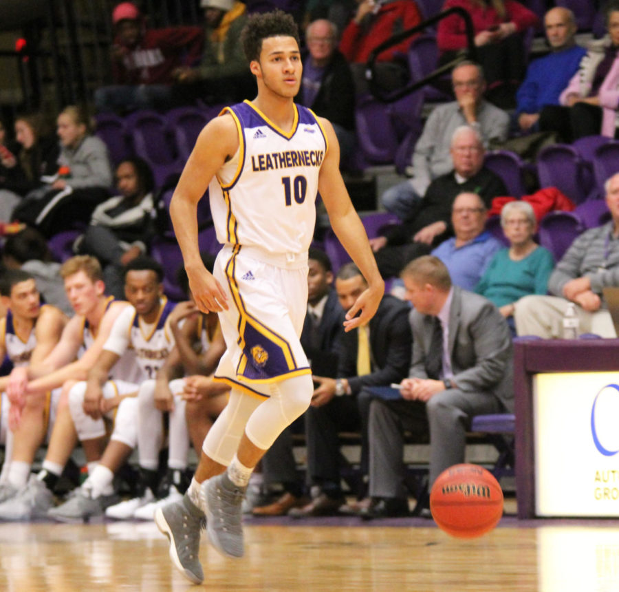 Kobe Webster eyes the defense as he dribbles up court.