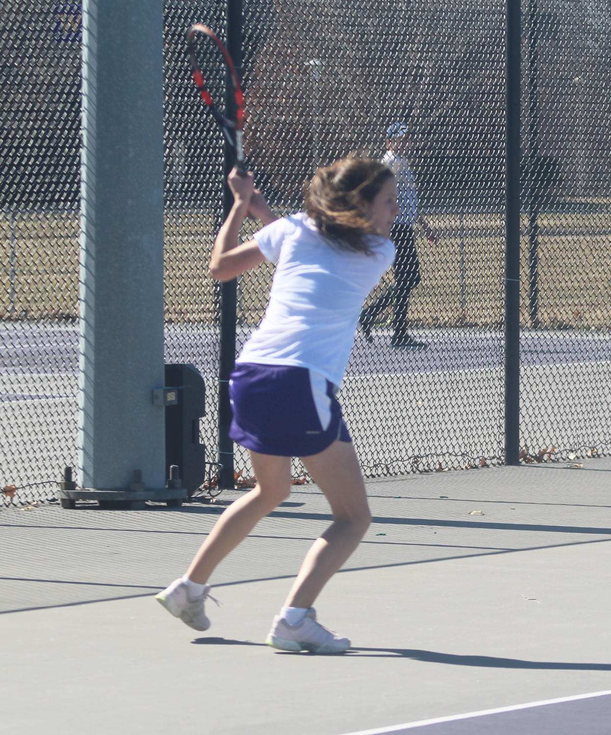 Mary Bjelica swings her racket in a singles match at home.