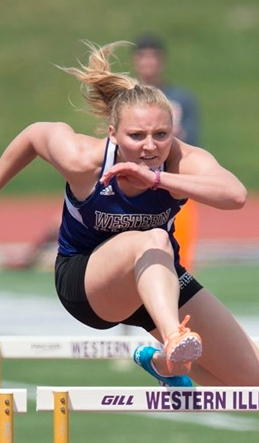 Michaela Busch racing in hurdle event at meet.