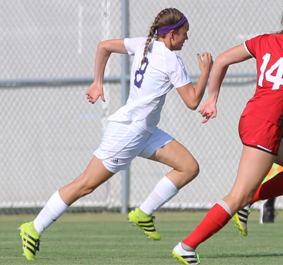 Emily Bollman sprints alongside an opponent at a home game.