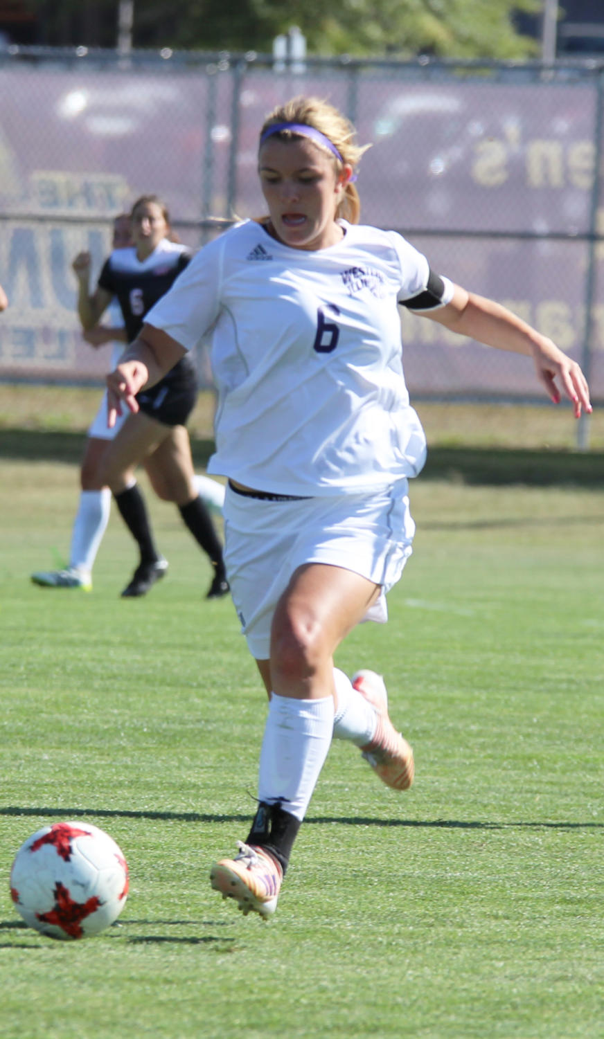 Madeline Edwards dribbles the ball down field.