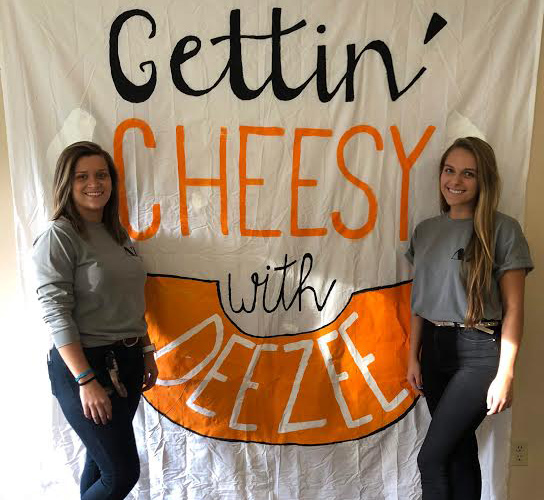 Sara Remar and Madison Brewer stand in front of their sign.