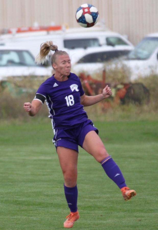 Maddie Wilsey heads the ball while playing in the defense.